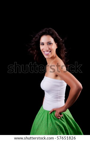 young and beautiful woman smiling, with her hair in the wind, isolated on black background - stock photo