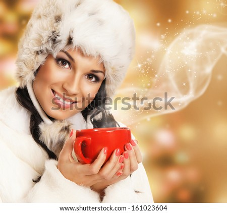 Young and beautiful woman with a red cup over abstract Christmas background - stock photo