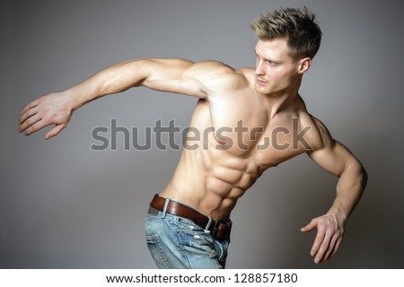 Young and blond athletic man is turning around - stock photo