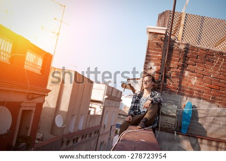 Young and brave man sitting on the edge on high roof looking far away, with backpack and skateboard (intentional sun glare) - stock photo
