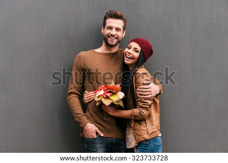 Young and carefree. Beautiful young couple bonding to each other and smiling while leaning at the grey wall - stock photo