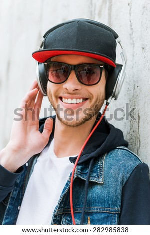 Young and carefree. Cheerful young man in headphones smiling at camera while leaning at the concrete wall  - stock photo