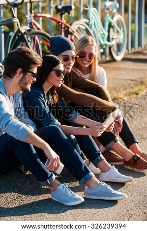 Young and carefree. Close-up of group of young smiling people bonding to each other and looking at digital tablet while sitting outdoors together with bicycles in the background - stock photo