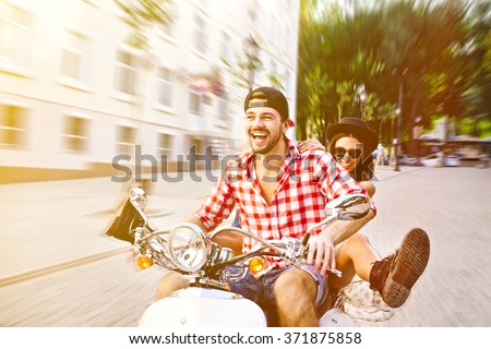 Young and carefree couple riding a scooter on on city streets. Speed blur effect. - stock photo