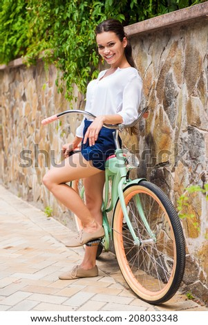 Young and carefree. Full length of beautiful young woman leaning at her vintage bicycle and smiling  - stock photo