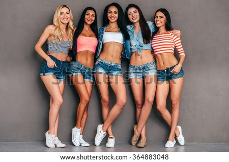 Young and carefree. Full length of five beautiful young women bonding and smiling while standing against grey background - stock photo