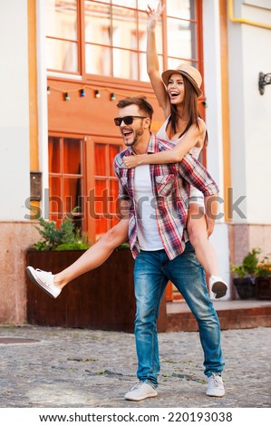 Young and carefree. Full length of happy young man carrying his beautiful girlfriend on shoulders and smiling while walking by the street - stock photo
