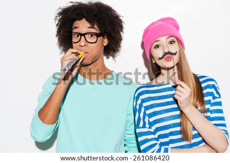Young and carefree. Funky young couple making faces while standing against white background  - stock photo