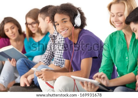 Young and carefree. Group of multi-ethnic students spending time together while isolated on white - stock photo