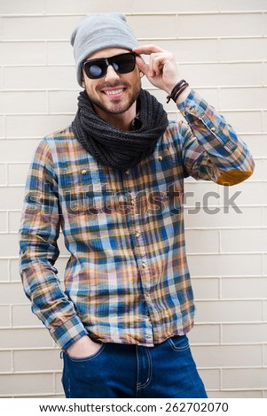 Young and carefree. Handsome young man adjusting his sunglasses and smiling while standing against brick wall  - stock photo