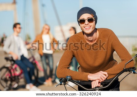 Young and carefree. Handsome young man leaning at his bicycle and looking at camera with smile while his friends talking in the background  - stock photo