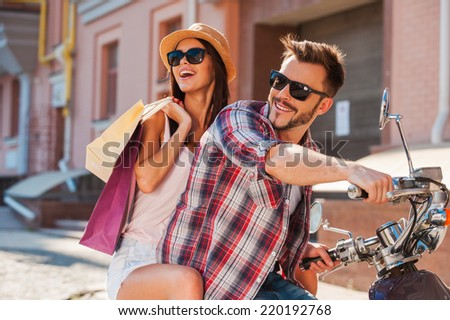 Young and carefree. Side view of beautiful young couple riding scooter together while happy woman carrying shopping bags and bonding - stock photo