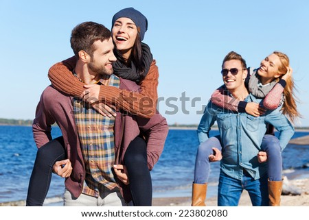 Young and carefree. Two beautiful young couples walking by the beach and smiling - stock photo