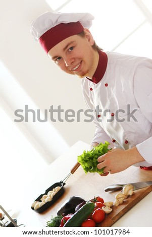Young and cheerful chef on the kitchen - stock photo