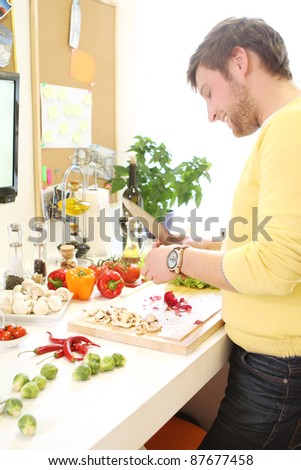 Young and cheerful woman cooking healthly food