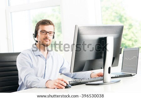 Young and confident customer support operator working in a call center office
