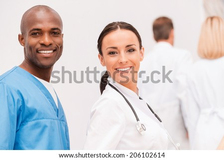 Young and confident doctors. Two cheerful doctors looking over shoulder and smiling while their colleagues moving up by staircase - stock photo
