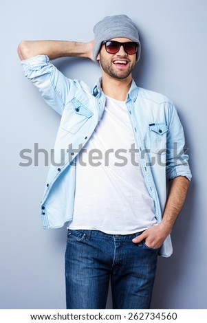 Young and cool. Handsome young stylish man in sunglasses and hat looking at camera and smiling while standing against grey background - stock photo
