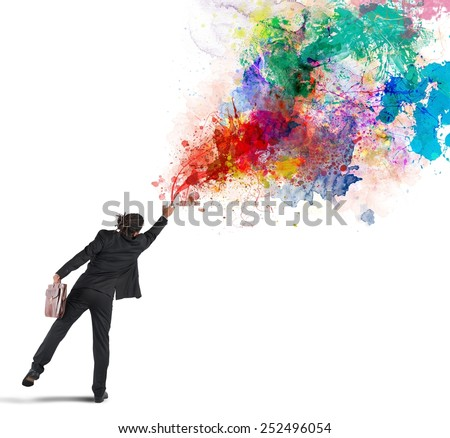 Young and creative businessman colors with spray - stock photo