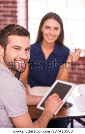 Young and creative colleagues. Two cheerful business people in casual wear sitting at the table together and looking at camera while man holding digital tablet  - stock photo