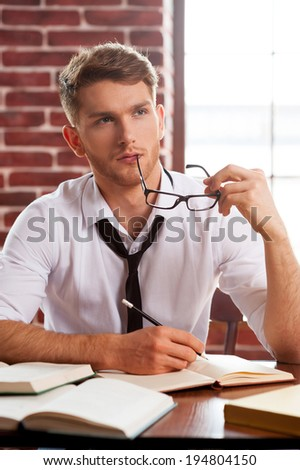 Young and creative. Thoughtful young man in shirt and tie writing something in note pad and looking away while sitting at his working place - stock photo