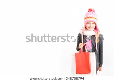 Young and cute shopping girl holding a red bag isolated on white background - stock photo