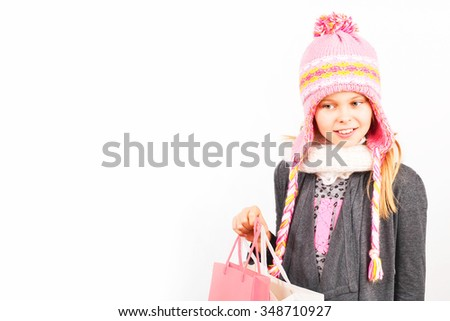 Young and cute shopping girl holding a red bag isolated on white background