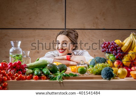 Young and cute woman sitting at the table full of fruits and vegetables in the wooden interior. Healthy food concept. Beauty and wellbeing - stock photo