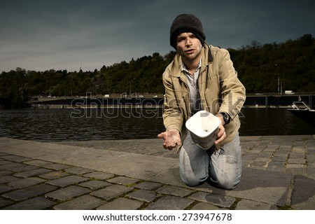 Young and dirty beggar asking for some money on city river bank - stock photo