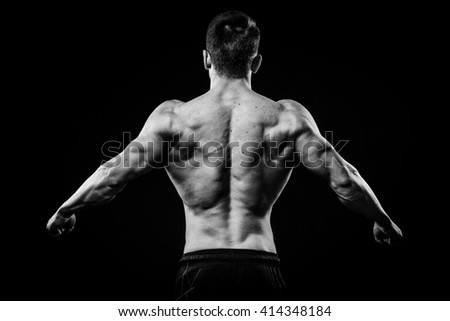 Young and fit bodybuilder athlete demonstrates biceps back view isolated on black background - stock photo