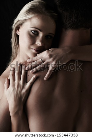 Young and fit caucasian adult couple in an embrace. Semi-nude and topless against a dark background . - stock photo