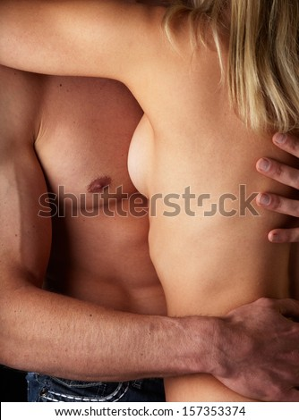 Young and fit caucasian adult couple in an embrace. Semi-nude and topless against a dark background .