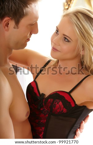 Young and fit caucasian adult couple in an embrace. Semi-nude and topless on a bed in a light bedroom with the woman wearing a sexy red and black lace corset and the man wearing only blue jeans. - stock photo