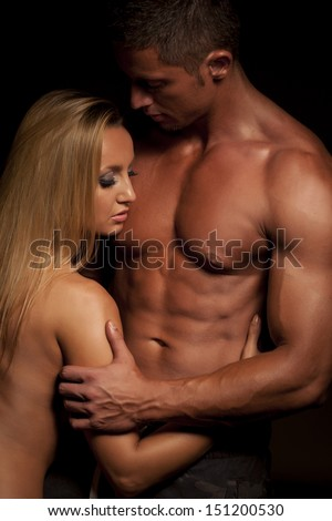 Young and fit topless couple in an embrace on dark background - stock photo