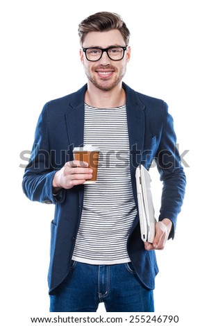 Young and full of ideas. Cheerful young man holding laptop and cup of coffee while standing against white background - stock photo