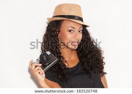 Young and funky. Beautiful young African woman in funky hat holding camera and smiling while standing against white background - stock photo