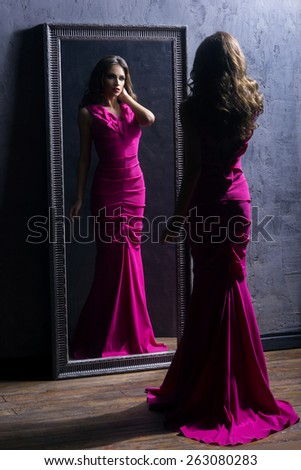 Young and gorgeous actress in a long dress preparing in a dressing room in front of a mirror.
