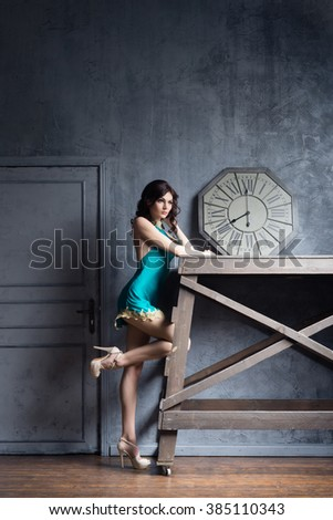 Young and graceful woman posing in a fashion lingerie. Ancient interior with a vintage clock.