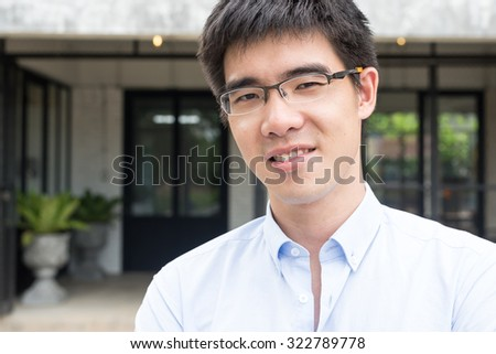 young and handsome asian business man smiling at the camera