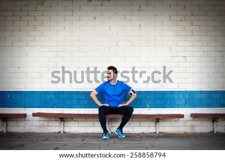 young and handsome athlete sitting and resting on the bench - stock photo
