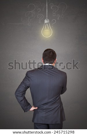 Young and handsome businessman thinking in front of light idea bulb and question marks concept - stock photo