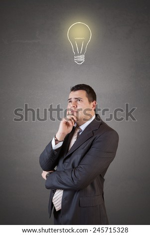 Young and handsome businessman thinking in front of light idea bulb concept