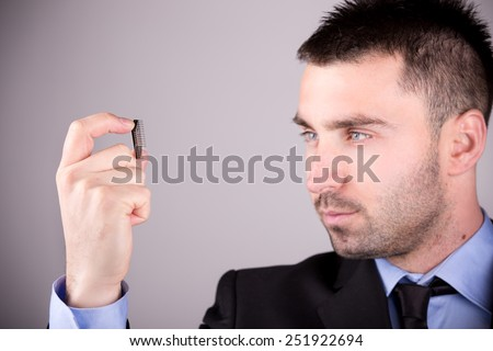 Young and handsome electronic engineer holding computer microchip. Focus on chip - stock photo