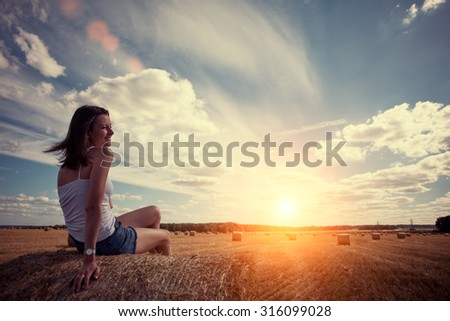 Young and handsome girl sitting on haystack in the field at sunset (intentional sun glare)