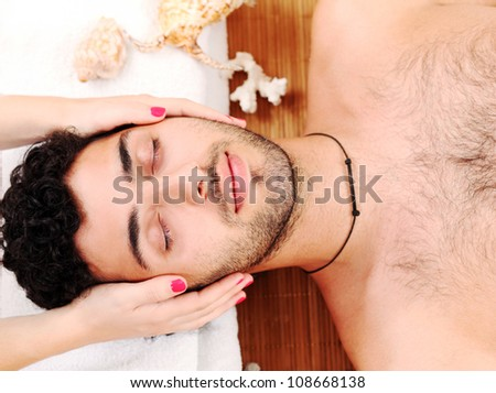 Young and handsome guy enjoying massage therapy - stock photo