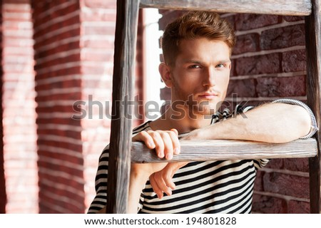 Young and handsome. Handsome young man in striped shirt leaning at the wooden ladder and looking at camera while standing near the brick wall - stock photo