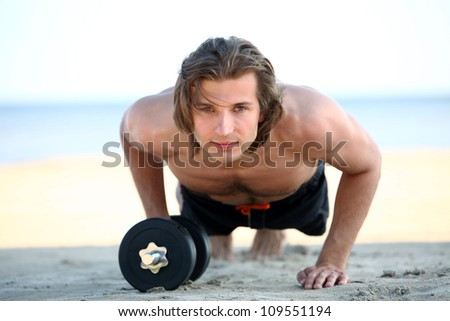 Young and handsome man doing fitness exercises on the beach