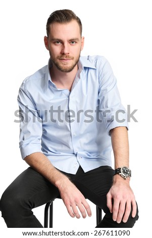 Young and handsome man in his 20s wearing a blue shirt sitting down on a chair in a studio setting. White background. - stock photo