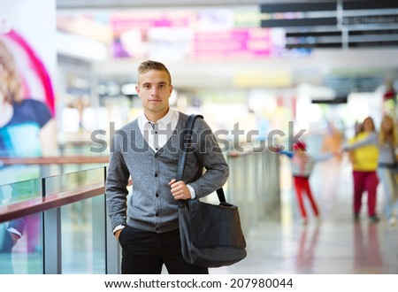 Young and handsome man is walking in shopping mall - stock photo