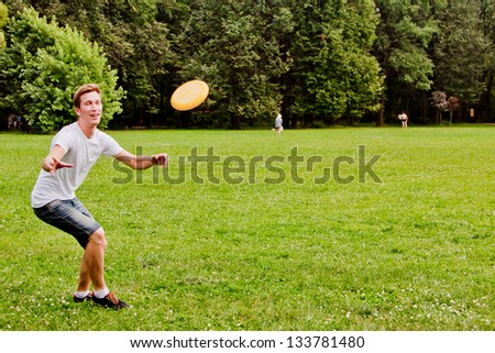 young and handsome man playing frisbee - stock photo